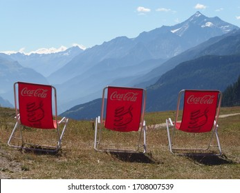 Maison Vieille, Alps, Italy: circa July 2017: Red beach chair with logo Coca Cola in mountain viewpoint near shelter Maison Vieille in Italian Alps