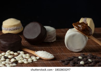maizena alfajores with coconut white and dark chocolate with dulce de leche and wooden spoon with sweet caramel on wooden bottom