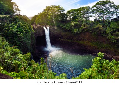 Majesitc Rainbow Falls waterfall in Hilo, Wailuku River State Park, Hawaii. The falls flows over a natural lava cave, the mythological home to Hina, an ancient Hawaiian goddess.