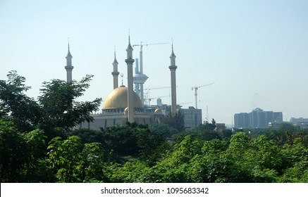 The majestic Abuja National Mosque in Nigeria's capital behind green trees taken in afternoon. Built in 1984 with 4 minarets and big golden dome in the centre. Islam is one of the main religions.