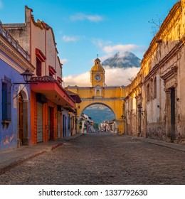 The majestic Agua volcano and Antigua city main street at sunrise with the colorful Santa Catalina arch in colonial style architecture, Guatemala.