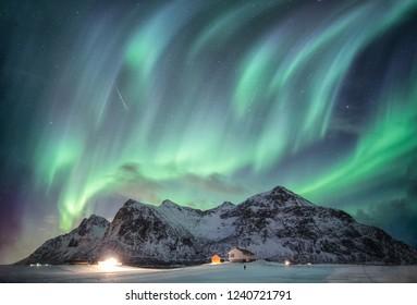 Majestic Aurora borealis with starry over snow mountain range with illumination house in Flakstad, Lofoten islands, Norway