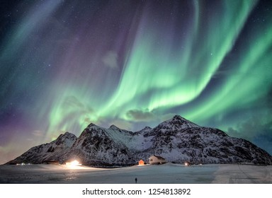 Majestic Aurora borealis with starry over snow mountain range with illumination house in Flakstad, Lofoten islands, Norway