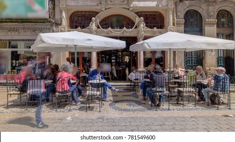 Majestic cafe facade in Porto Portugal. People sitting outside under umbrellas.
