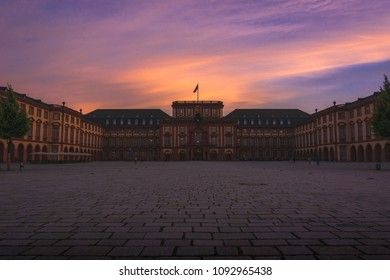 Majestic castle of Mannheim centered with colorful sky and empty atrium.