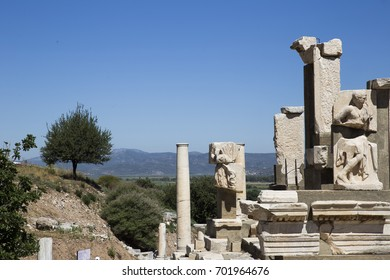 Majestic columns and ruins of the ancient city of Ephesus against the backdrop of tree-covered hills of the blue sky and mountains in the distance