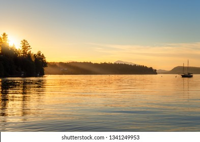 Majestic Golden Sunset over a Bay with with Wooded Coastline and an Anchored Sailing Boat