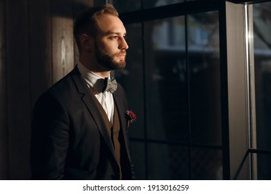 Majestic handsome man with a beard, dressed in a classic suit and bow tie. Profile portrait and piercing gaze of a wise man. Red rose as a decoration on a jacket. Free space for text
