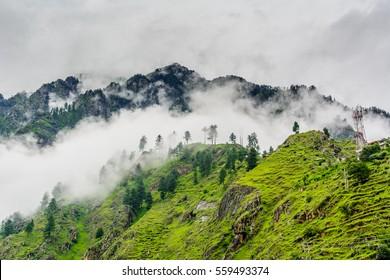 Majestic Himalayan mountains covered with lush green forest and clouds in monsoon