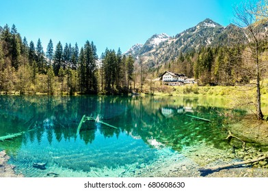 Majestic mountain lake in the Alps. Traditional house at waterside.
