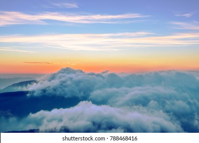 Majestic mountains sunrise with ground covered by clouds and luminous colors of sky on horizon