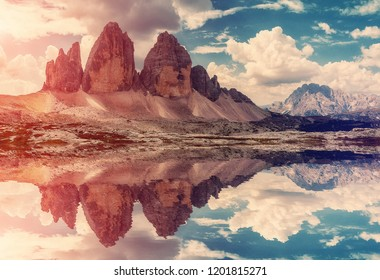 Majestic nature  landscape. Beautiful view of famous Tre Cime di Lavaredo mountains in the Dolomites mountain during sunset with reflected in water. South Tyrol, Italy. Stunning nature scenery