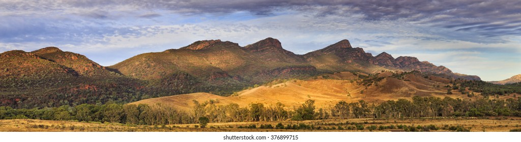 Majestic panorama of WIlpena Pound mountain range in Flinders ranges. Taken at sunrise with soft warm light on sides of hills and peaks