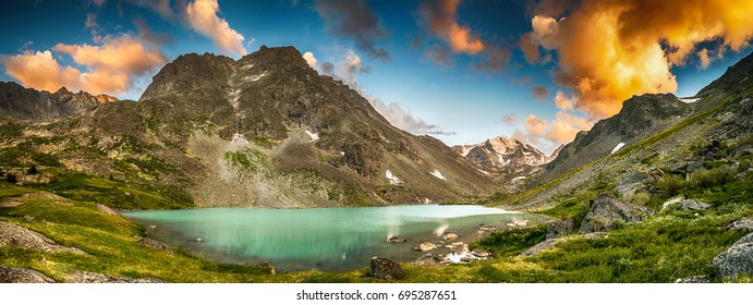 Majestic panoramic view on mountain lake surrounded by mountain ridge during sunset, Belukha national park, Altai republic, Siberia, Russia