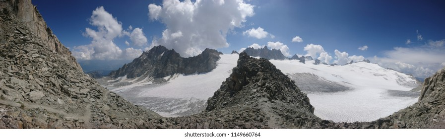 Majestic rugged craggy panorama overlooking two Alpine glaciers : Plateau du Trient and Orny Glacier on a beautiful Summer afternoon in Swiss Alps with a few clouds in the horizon