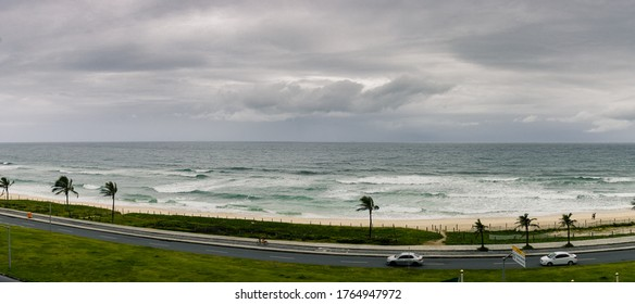 Majestic Seascape of beach, waves, cars, clouds and cyclist on a cloudy day