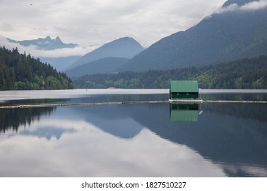 A majestic shot of a Cleveland Dam reservoir with a boat house on the lake and Lions mountains on the horizon