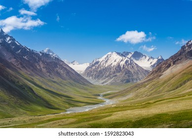 Majestic snow capped mountains or glacier landscape with green alpine meadows and stream running in valley under blue sky in Khunjerab of Karakoram Mountains in Pamirs plateau of central Asia
