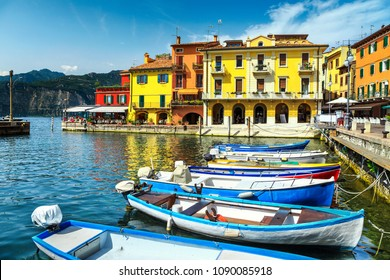 Majestic summer landscape, colorful boats and typical Italian buildings in spectacular harbor, Malcesine tourist resort, lake Garda, Veneto region, Italy, Europe