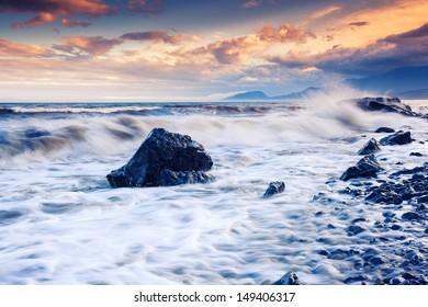 Majestic summer sunset over the stormy sea. Dramatic overcast sky. Crimea, Ukraine, Europe. Beauty world.