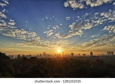 Majestic sunrise over Kuala Lumpur skyline with sun rays