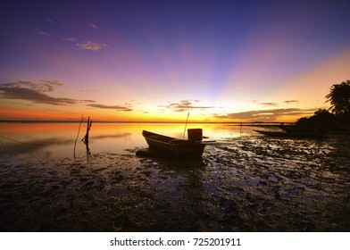 The Majestic sunrise of the seascape with morning rays and fisherman boat as point of interest. motion to sky and vibrant color.