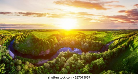 Majestic sunset in the nature landscape. Aerial panorama of blue calm river in the forest and fields at the sunset. Summer nature landscape. Dramatic cloudy sky. View of nature forest landscape