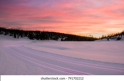 Majestic Sunset in the winter mountains landscape. Silhouette of a forest. Field covered with snow. Ski track. HDR image. Norway