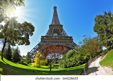 The majestic symbol of Paris - the Eiffel Tower lit hot summer sun. At the foot of the tower is designed park with paths and pond. The picture was taken Fisheye lens