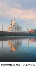 Majestic Taj Mahal marble glowing orange and red mosque beautifully reflected in the gentle Jamuna river on a calm morning at sunrise from rear river view in Agra, India. Vertical copy space