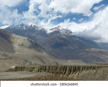 Majestic Upper Mustang of Himalayas, Nepal, valley Kali Gandaki. Rock face with caves above Kagbeni. Barren mountain desert landscape. Thorong La pass. Vastness of snow Annapurna range.Pristine nature