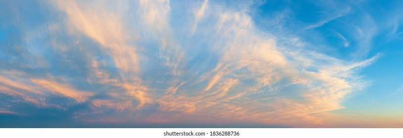 Majestic vanilla sky at evening. Azure sunset heaven with golden pink cirrus clouds over the horizon. Panoramic shot of pastel colored skyscape. Beauty in nature.