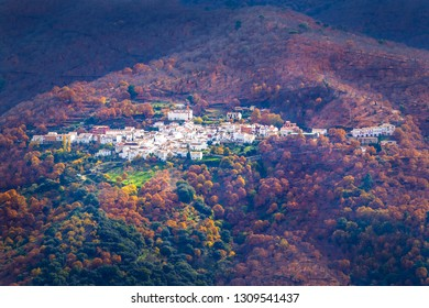 Majestic view of beautiful remote mountains in clouds and sunlight with town on hillside. Parauta in Malaga, Spain