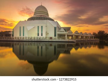 Majestic view of An Nur Mosque during fiery sunrise with stunning reflections and awesome sky background. Blur due to long exposure.