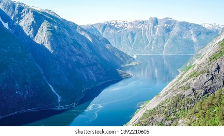 A majestic view on Eidfjord from Kjeasen, Norway. Slopes of the mountains are overgrown with lush green grass. Water has dark blue color. Taller parts of the mountains are barren. Sunny and clear day