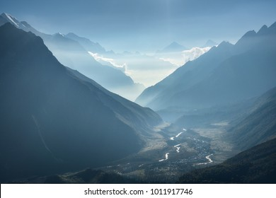 Majestic view of silhouettes of mountains and low clouds at sunset in Nepal. Landscape with high rocks of Himalayan mountains, beautiful blue sky and sun rays. Amazing Himalayas. Nature background