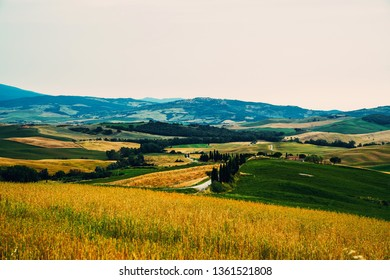 Majestic view of typical Tuscany countryside nature landscape. Beautiful hills at the sunrise time, fields and rural road. Italy, Europe. Holiday, traveling concept.