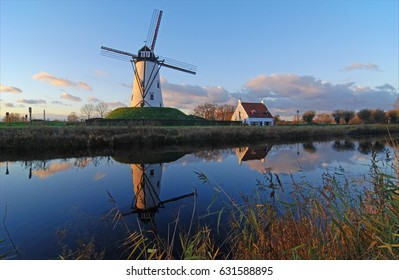 The majestic windmill in the city of Damme at sunset reflecting in a nearby canal near Bruges, Belgium.
