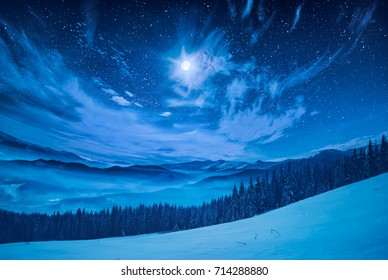 Majestic winter night in a mountain valley with full moon in a starry sky.