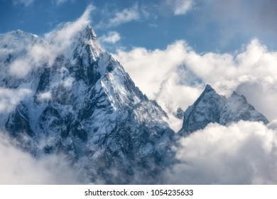 Majestical scene with mountains with snowy peaks in clouds in Nepal. Landscape with beautiful high rocks and dramatic cloudy sky in sunny bright day. Nature background. Vintage. Amazing Himalayas