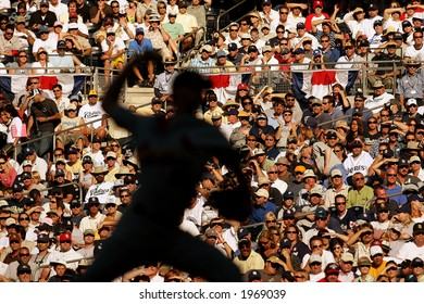 A major league baseball pitcher throws with a sunlit crowd behind him at Petco Park in San Diego.