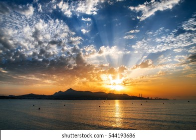 Majorca Puerto de Alcudia beach pier at sunrise in Alcudia bay in Mallorca Balearic islands of Spain. Sun rises over the mountains in the sea
