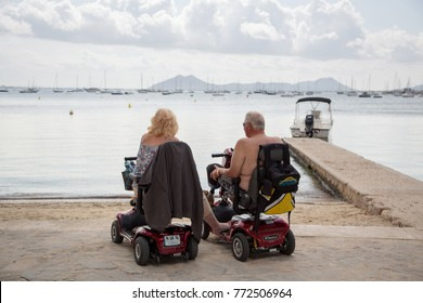 Majorca, Spain, Europe - September 26, 2017. Senior couple on mobility scooters looking out to the sea. Disabled older man and woman enjoying summer vacation holidays