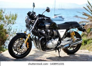 Majorca, Spain - May 29, 2019: On foreground lonely Honda CB1100 model modern naked bike, on background yachts moored on Mediterranean waters. Most convenient movement on the island on a motorcycle