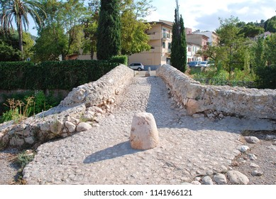 MAJORCA, SPAIN - SEPTEMBER 4, 2017: The Roman bridge across the Torrente de Sant Jordi at Pollenca on the Spanish island of Majorca. The actual origin of the bridge is unconfirmed.