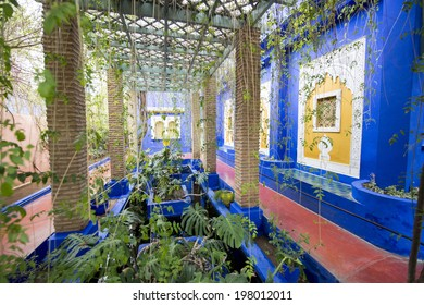 MAJORELLE GARDEN, MARRAKECH, MOROCCO, MAY 11, 2014. A pond with gold fishes, and the yellow window frames of the former blue house of Yves Saint-Laurent, in Marrakech, Morocco, on May 11th, 2014.