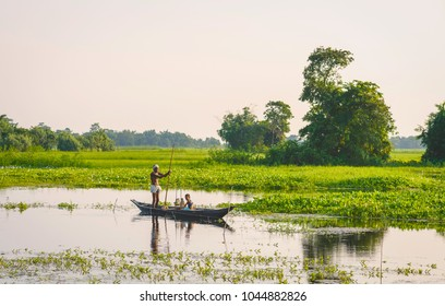MAJULI, INDIA - AUGUST 27, 2011: Father and son set nets and traps for shell fish at dawn in a lagoon in their tradition dugout wooden boat on August 27, 2011, Majuli Island, Assam, India.