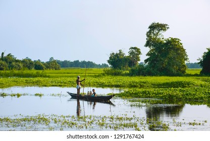 MAJULI, INDIA - AUGUST 27, 2011: Father and son set nets and traps for shell fish at dawn in a lagoon in their traditional dugout wooden boat on August 27, 2011, Majuli Island, Assam, India.