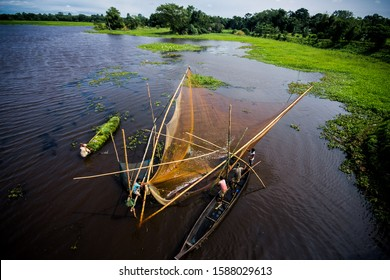 Majuli,Assam,India - Oct 10 2015: Fishermen setting up complex fishing Chinese nets over marshlands of Majuli