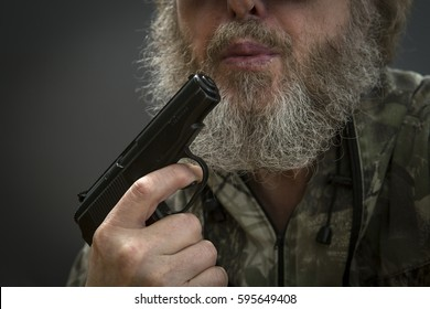 Makarov pistol in  hand aggressive men  on   against a dark background.